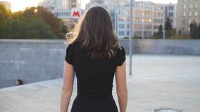 Ung oigenkännlig flicka i svart klänning som promenerar den stads- gatan Attraktiv affärskvinna som går i stad flicka lager videofilmer