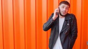 Ung orakad caucasian man i ett svart omslag som talar på telefonen på en orange bakgrund, långsam-mo, innegrej lager videofilmer
