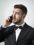 Ung orakad uppriven affärsman på telefonen som ser upp Royaltyfri Foto