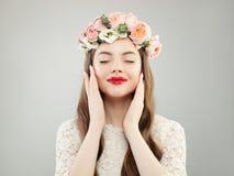 Ung perfekt modell Woman Enjoying Spring Härlig flicka med lockigt hår, makeup och att koppla av för blommor royaltyfria bilder