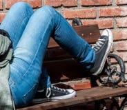 Ung person med jeans och gymnastikskor som ner ligger på en träbänk med bakgrund för röda tegelstenar royaltyfri bild