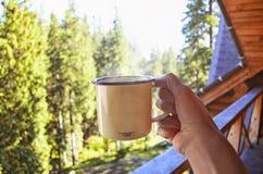 Ung person med kopp te, kaffe som står på farstubron av hotellbalkongen arkivfoto