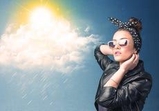 Ung person som ser med solglasögon på moln och solen Arkivbild