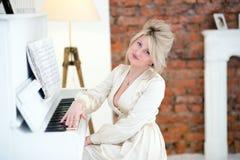 Ung pianist i aftonklänning Arkivbild
