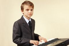 Ung pianist i dräkten som spelar det digitala pianot Royaltyfri Foto