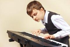 Ung pianist i dräkten som spelar det elektroniska organet Arkivfoton