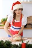 Ung pizza för brunettkvinnamatlagning eller handgjord pasta, medan bära det Santa Claus locket i köket Hemmafrupreparin Arkivbild