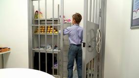 Ung pojkeöppning av valvdörren i banken arkivfilmer