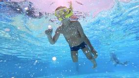 Ung pojke, barnbad i en pöl med en gul maskering Undervattens- l?ngd i fot r?knat lager videofilmer