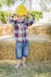 Ung pojke för blandat lopp som skrattar med den hårda hatten utanför Arkivbilder