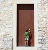 Ung pojke framme av en stor dörr Royaltyfria Bilder