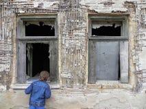 Ung pojke framme av ett gammalt fönster Arkivfoto