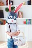 Ung pojke i den polygonal maskeringen för easter kaninkanin som mycket poserar med en korg av ägg arkivbild