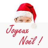 Ung pojke i den röda jultomtenhatten och Joyeux Noel royaltyfria bilder