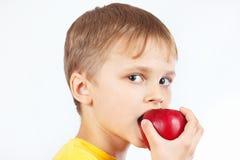 Ung pojke i en gul skjorta som äter det mogna röda äpplet Arkivfoto