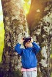 Ung pojke i ett blått lag som ser till och med kikare Royaltyfri Foto