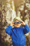 Ung pojke i ett blått lag som ser till och med kikare Fotografering för Bildbyråer