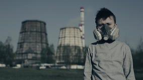 Ung pojke i gasmaskrespirator mot den industriella tagna closeupen för röka rör Milj?belastningbegrepp stock video