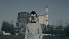 Ung pojke i gasmaskrespirator mot den industriella tagna closeupen för röka rör Milj?belastningbegrepp lager videofilmer
