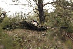 Ung pojke i kamouflage med ett vapen, lasertag Arkivbilder
