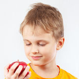 Ung pojke i orange skjorta med det röda äpplet Arkivfoton