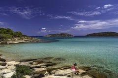 Ung pojke i tillfälligt avslappnande sammanträde på sommarhavet Arkivfoton