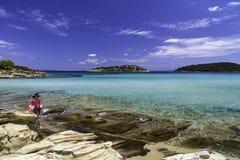 Ung pojke i tillfälligt avslappnande sammanträde på sommarhavet Arkivbild