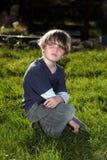 Ung pojke i trädgården som ser över hans skuldra Arkivbild