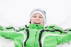 Ung pojke i vintersnö som skrattar med njutning Arkivbild