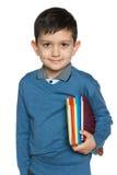 Ung pojke med böcker Arkivbild