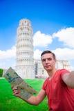 Ung pojke med den toristic översikten på lopp till Pisa Turist- resande som besöker det lutande tornet av Pisa fotografering för bildbyråer