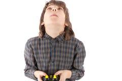 Ung pojke med fjärrkontroll som ser upp medan honom som kör hans dr Royaltyfri Foto