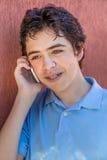 Ung pojke med hänglsen på telefonen Fotografering för Bildbyråer