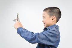 Ung pojke med lyckligt och leende med sedeln Fotografering för Bildbyråer