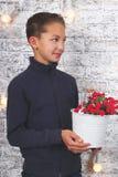 Ung pojke med röda blommor Royaltyfri Fotografi