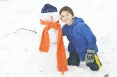 Ung pojke med snögubben arkivbild