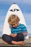 Ung pojke med surfingbrädan Royaltyfri Bild