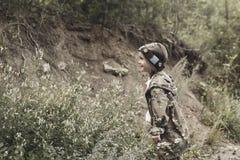 Ung pojke med vapnet, laser-etikett, krigsimulering Arkivfoton