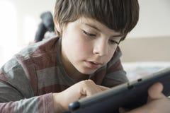 Ung pojke och en digital minnestavla Royaltyfri Bild