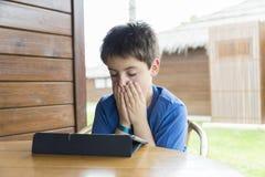Ung pojke och en digital minnestavla fotografering för bildbyråer