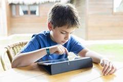 Ung pojke och en digital minnestavla Arkivbilder