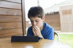 Ung pojke och en digital minnestavla Arkivfoton