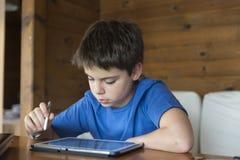 Ung pojke och en digital minnestavla Royaltyfri Fotografi