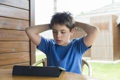 Ung pojke och en digital minnestavla Royaltyfria Foton