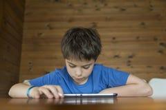 Ung pojke och en digital minnestavla arkivbild