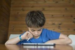 Ung pojke och en digital minnestavla arkivfoto
