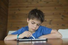 Ung pojke och en digital minnestavla royaltyfri foto