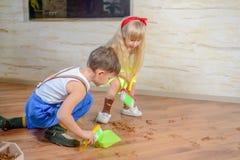 Ung pojke och flicka som hjälper att göra ren huset fotografering för bildbyråer
