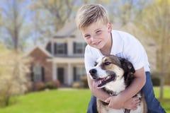 Ung pojke och hans hund framme av huset