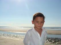Ung pojke på en strand Arkivfoto